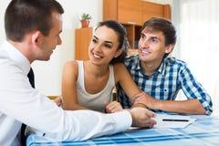 Vendeur sûr et jeunes conjoints discutant le contrat Photographie stock libre de droits