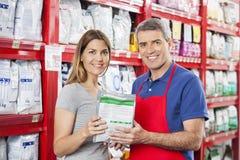 Vendeur Selling Pet Food au client dans la boutique photographie stock