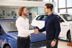 Vendeur serrant la main au client au concessionnaire image libre de droits