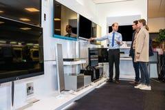 Vendeur Showing Flat Screen TV à coupler dans le magasin Photo stock