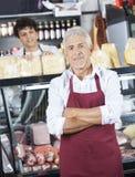 Vendeur Standing Arms Crossed tandis que collègue travaillant chez Counte Image libre de droits