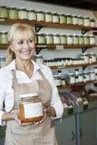 Vendeur supérieur heureux avec le pot regardant loin dans le magasin d'épice Photos stock
