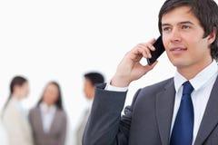 Vendeur sur son téléphone portable avec l'équipe derrière lui Photos libres de droits
