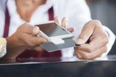 Vendeur Swiping Credit Card au téléphone portable Photographie stock libre de droits
