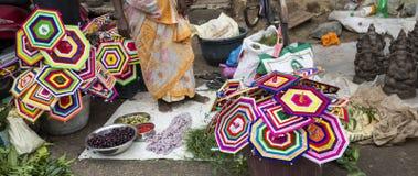 Vendeur vendant les fleurs fraîches, légumes, fruits, parapluie pour que les passionnés bénissent un dieu indou Ganesh au marché  Photos libres de droits