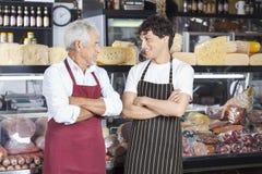 Vendeurs avec des bras croisés dans la boutique de fromage Photos stock