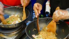 Vendeurs faisant cuire les nouilles faites sauter à feu vif à vendre sur un marché local, Thaïlande banque de vidéos