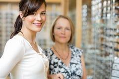 Vendeuse avec la femme supérieure dans l'opticien Store Photos stock