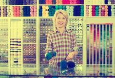 Vendeuse de femme dans le magasin de couture images stock