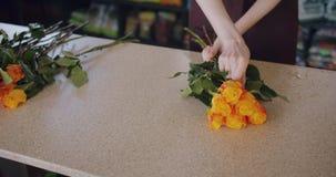 Vendeuse de fleurs faisant la belle composition des roses travaillant dans le magasin banque de vidéos