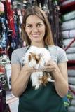 Vendeuse heureuse Holding Guinea Pig au magasin Photographie stock libre de droits