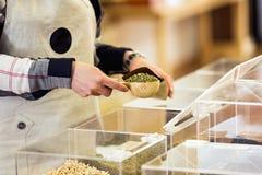 Vendeuse mettant le soja dans un panier en vrac dans un magasin organique Images stock