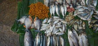 Vendiendo peces de agua salada y las gambas encima de la hoja Jakarta admitida foto Indonesia del plátano foto de archivo