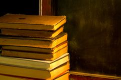 Vendimia, libros antiguos al lado de la pizarra vieja en la escuela pintada Fotografía de archivo
