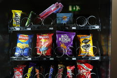 Vending machine goods. Snacks and sweets cookies in vending machine bright packaging dark background Royalty Free Stock Photography