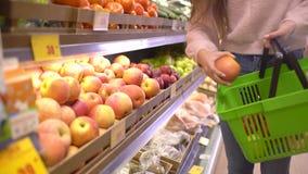 Vendita, acquisto, alimento, consumismo e concetto della gente - donna con le mele d'acquisto della borsa alla drogheria stock footage