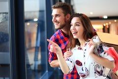 Vendita, consumismo e concetto della gente - giovane coppia felice con i sacchetti della spesa che camminano nel centro commercia fotografia stock libera da diritti