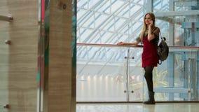 Vendita, consumismo: Giovane donna con gli smartphones ed i sacchetti della spesa che stanno e che parlano vicino al centro comme stock footage