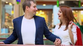 Vendita, consumismo, tecnologia e concetto della gente - giovane coppia felice con i sacchetti della spesa La giovane conversazio stock footage
