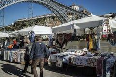 Vendita delle merci locali sulla sponda del fiume con la vista sopra il ponte di Luis I, Oporto, Portogallo Fotografia Stock