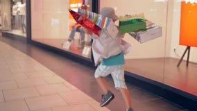 Vendita di autunno, bambino di modo con i sacchetti della spesa nella fretta per ottenere sconto in boutique archivi video