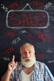 Vendita di pubblicità invecchiata dell'uomo facendo uso delle iscrizioni del gesso sulla lavagna Immagini Stock