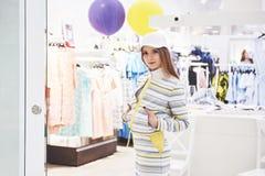 Vendita, modo, consumismo e concetto della gente - giovane donna felice con i sacchetti della spesa che scelgono i vestiti in cen fotografia stock libera da diritti