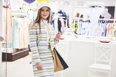 Vendita, modo, consumismo e concetto della gente - giovane donna felice con i sacchetti della spesa che scelgono i vestiti in cen immagine stock libera da diritti