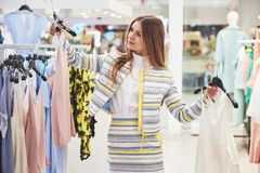 Vendita, modo, consumismo e concetto della gente - giovane donna felice con i sacchetti della spesa che scelgono i vestiti in cen fotografia stock
