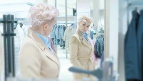 Vendita, modo, consumismo e concetto della gente - sacchetti della spesa della donna che scelgono i vestiti in centro commerciale video d archivio