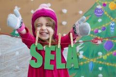 Vendita, natale, feste e concetto della gente - il bambino sorridente in vestito rosso con la vendita firma Fotografia Stock Libera da Diritti