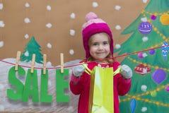 Vendita, natale, feste e concetto della gente - il bambino sorridente in vestito rosso con la vendita firma e borse Fotografie Stock Libere da Diritti