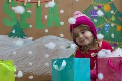 Vendita, natale, feste e concetto della gente - il bambino sorridente in vestito rosso con la vendita firma e borse Fotografia Stock