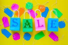 Vendita scritta sui sacchi di carta di acquisto circondati dalla vendita variopinta Fotografia Stock Libera da Diritti