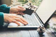 Vendite di natale Acquisto della donna con la carta di credito dal computer portatile nell'interno domestico Natale Feste di pial fotografia stock libera da diritti