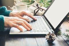 Vendite di natale Donna che scrive sul computer portatile nell'interno domestico Concetto di natale Feste di piallatura Ricerca d fotografia stock libera da diritti