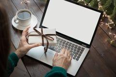 Vendite di natale Schermo come spazio per testo Regalo della tenuta della donna e scrivere dal computer portatile nell'interno do immagine stock libera da diritti