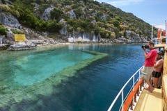 Vendite di una barca turistica dopo una sezione della città incavata fuori dall'isola di Kekova nella regione Mediterranea occide Fotografie Stock Libere da Diritti