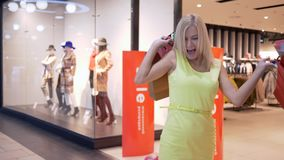 Vendite felici di acquisto, donna allegra che salta dal godere degli sconti nel deposito di modo mentre acquisti archivi video