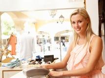Vendite femminili di aiuto nella memoria di vestiti Immagine Stock