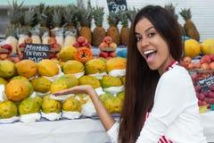 Venditora brasiliana di risata al mercato degli agricoltori con il franco tropicale Fotografia Stock