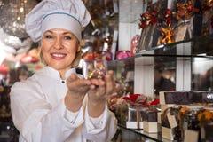 Venditora che posa con il cioccolato immagini stock