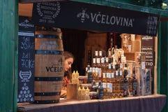 Venditora nella stalla con i prodotti dell'ape al mercato di Natale Fotografie Stock Libere da Diritti