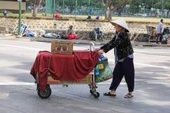 Venditore ambulante che spinge carretto attraverso la via Fotografie Stock