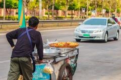Venditore ambulante non identificato che spinge un carretto mobile della cucina su una st Fotografia Stock