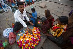 Venditore ambulante sulle banche del Gange sacro che vende i petali del fiore Fotografia Stock Libera da Diritti