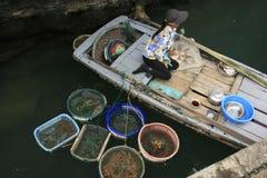 Venditore ambulante in una barca, baia di Halong, Vietnam Immagine Stock