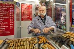 Venditore anziano della salsiccia con i baffi grigi che cucina l'alimento arrostito della carne di maiale e del vitello fotografia stock libera da diritti