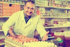 Venditore che posa con dozzine di uova immagini stock libere da diritti
