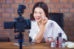 26a95fe756ca Venditore cosmetico online della giovane donna asiatica felice che vlogging  alla sua f immagine stock